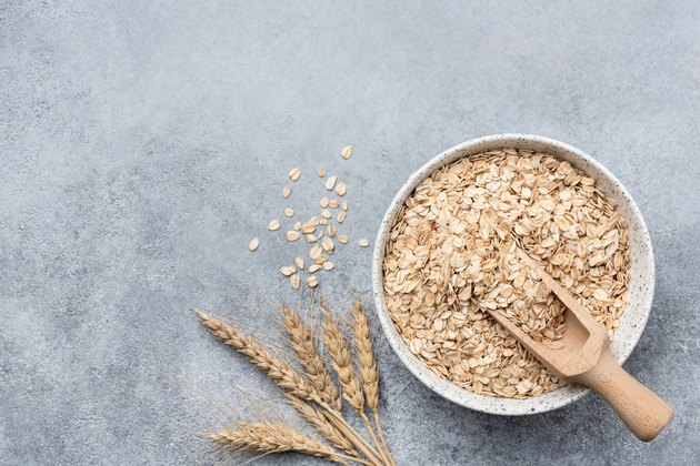 Rolled oats, oat flakes in bowl on concrete background