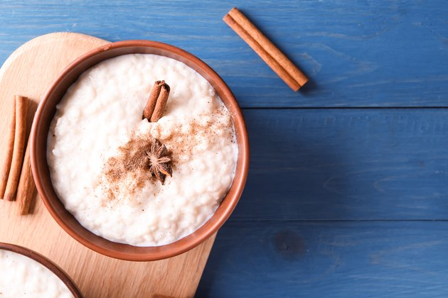 Delicious rice pudding with cinnamon and anise in bowl on wooden table