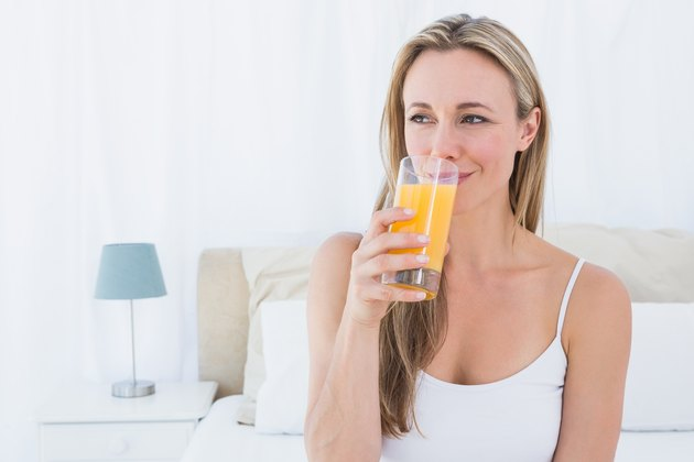 Woman drinking glass of vitamin C orange juice before going to sleep