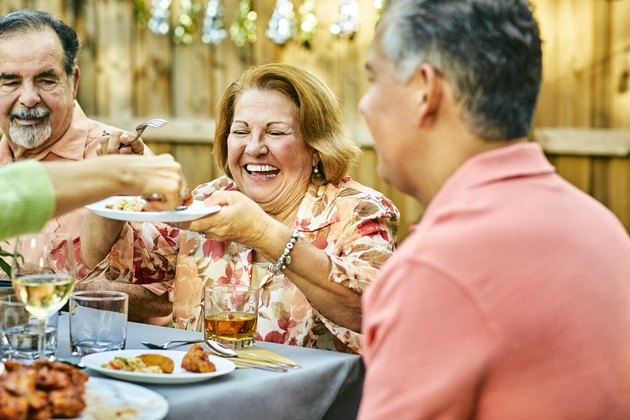 Cheerful family eating at table in back yard