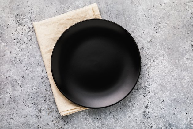 Empty ceramic plate in black with a napkin on a gray concrete table, top view