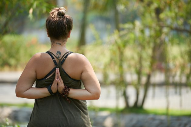 Back view of a woman doing yoga for weight loss outdoors near a river