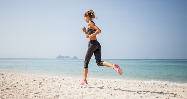Sporty woman running on the beach
