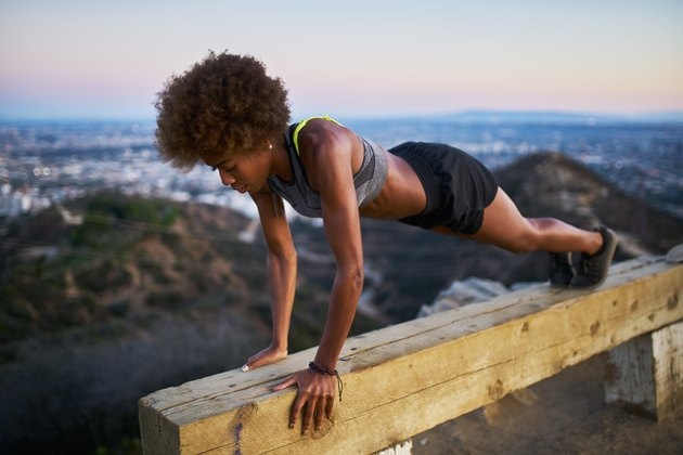 woman doing pushups on bench at runyon canyon after sunset