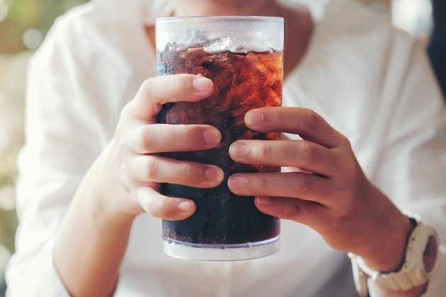 Close view of a woman's hands on a large glass of soda with ice