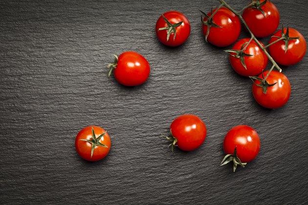 Tomatoes on black stone background