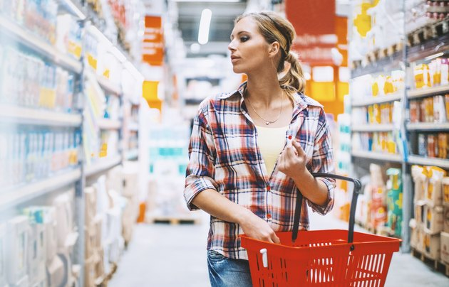 Woman at a supermarket shopping with a Kroger grocery list
