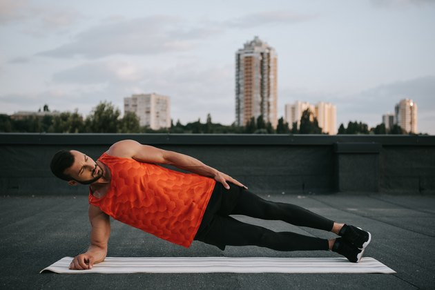 Cyclist doing cross-training strength-training exercise side plank on a rooftop