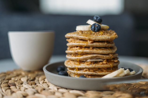 Side view of a stack of homemade pancakes on a plate, topped with blueberries and bananas