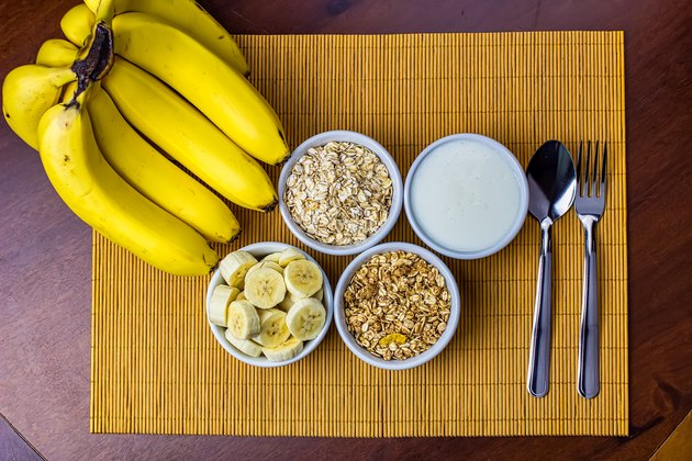 Banana sliced ramekin with oatmeal, granola and plain yogurt as side dishes under bamboo mat with bunch of bananas besides in top view