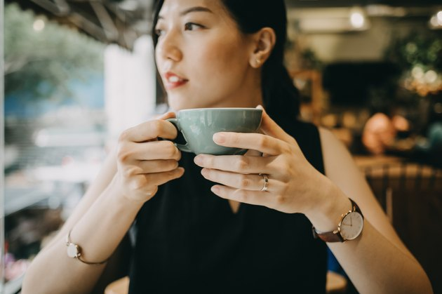 Young woman enjoying tea thinking about pro and cons of green tea