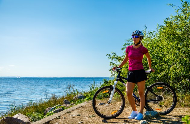 Woman cycling for exercise on trail near ocean
