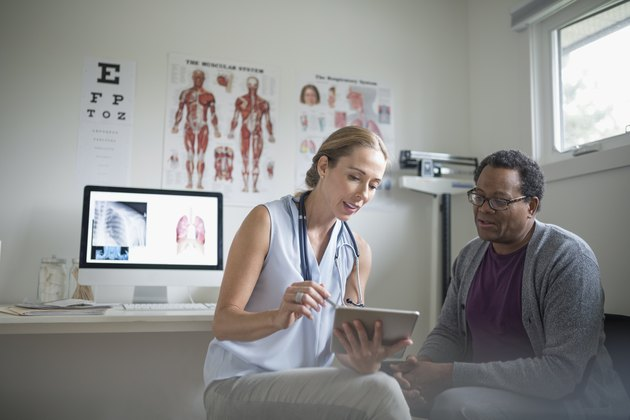 Female doctor with digital tablet talking with senior male patient in examination room