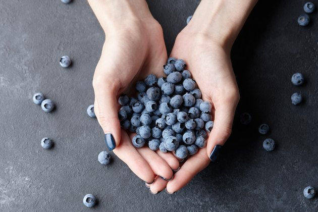 Close up of woman hands holding fresh blueberries