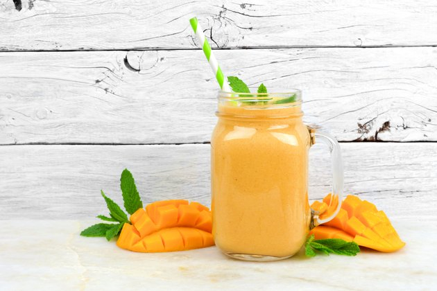 Mango coconut smoothie in a mason jar, on rustic white wood