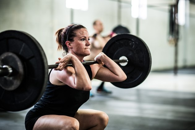 gym - Woman doing front squats in order to build muscle and burn fat