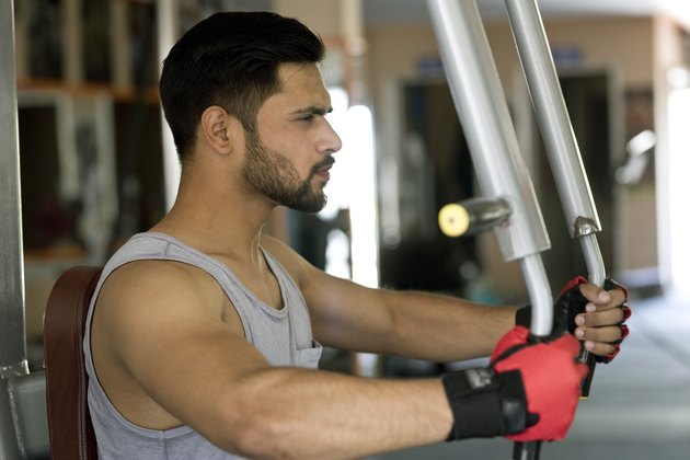 Young man doing chest exercise at gym