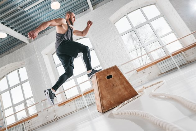 Strong man doing a box jump exercise at workout gym. Male athlete using box for gym exercises