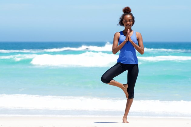 Healthy woman doing yoga exercise at beach