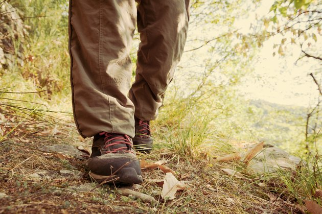 Hiking shoes with red laces and legs wearing long brown trousers of an hiker walking on a path in the wood. Vintage effect