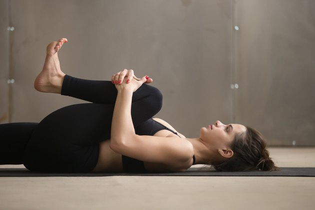 Young woman in Knees to Chest, Apanasana pose, studio, closeup