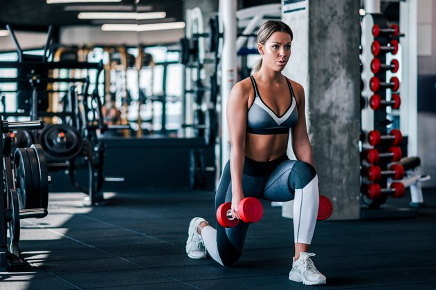 Young muscular woman doing Lunges during dumbbell butt workout