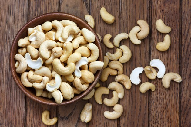Bowl of halved cashew nuts in a wooden bowl
