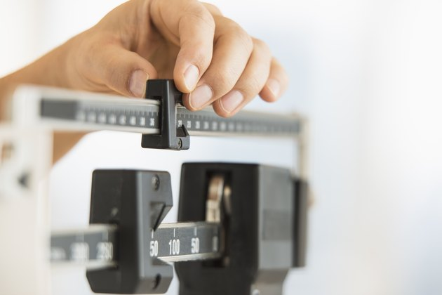 A hand adjusting the weight on a scale to represent obesity
