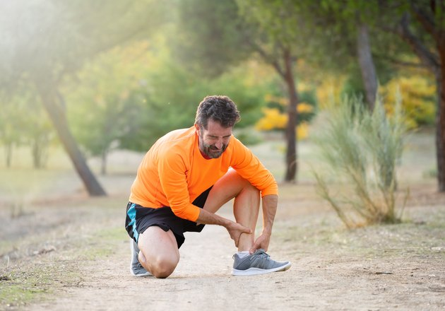 Athletic runner male holding leg with muscle cramp possibly due to potassium deficiency
