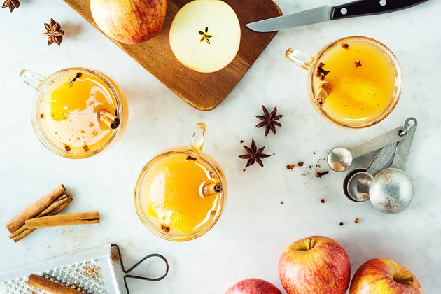 Mugs of Hot Spiced Mulled Apple Cider with Ingredients