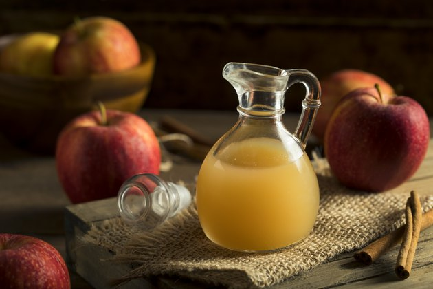 A small glass pitcher of raw apple cider vinegar on a table, surrounded by red apples