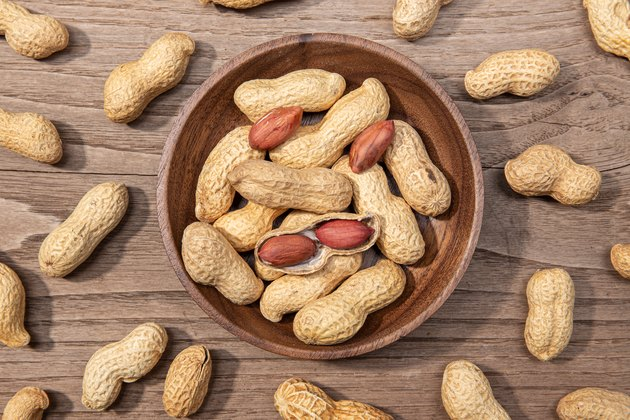 Peanuts in bowl on rustic wooden table
