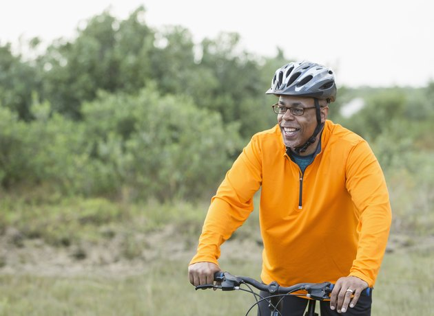 black man with glasses and helmet in orange pullover riding bike in park