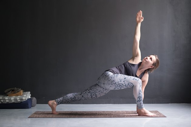 Woman practicing yoga, doing lunge exercise, Revolved Side Angle Pose