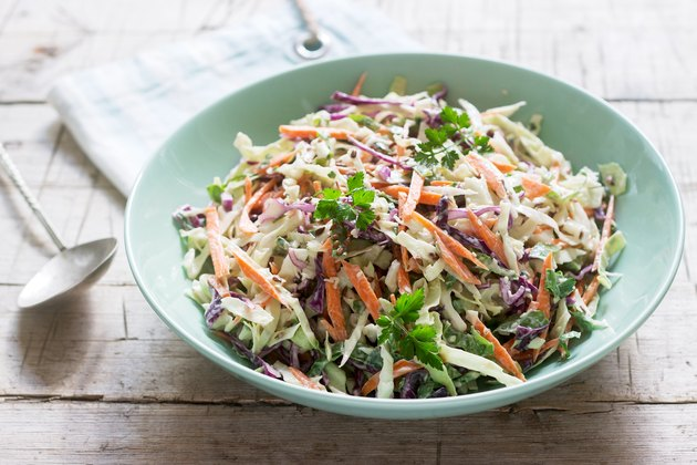 Coleslaw of cabbage, carrots and various herbs with mayonnaise in a large plate on a wooden background.