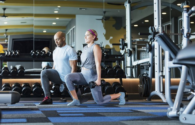Hispanic couple working out at the gym, doing lunges