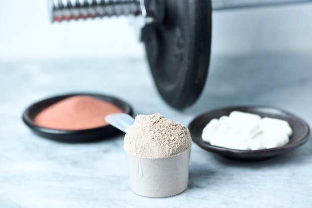 Scoop of Whey Protein, Beta-alanine capsules, Creatine Powder and a dumbbell in background. Sport nutrition. Stone / Wooden background. Copy space