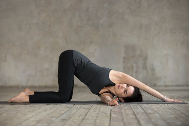 woman in black yoga clothes doing thread the needle shoulder and back stretch