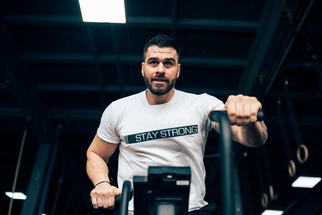 Man in a gym, training on an assault bike