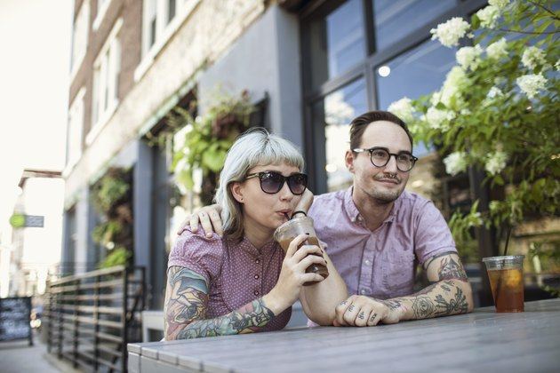 Young couple sitting in outdoor cafe drinking ice tea