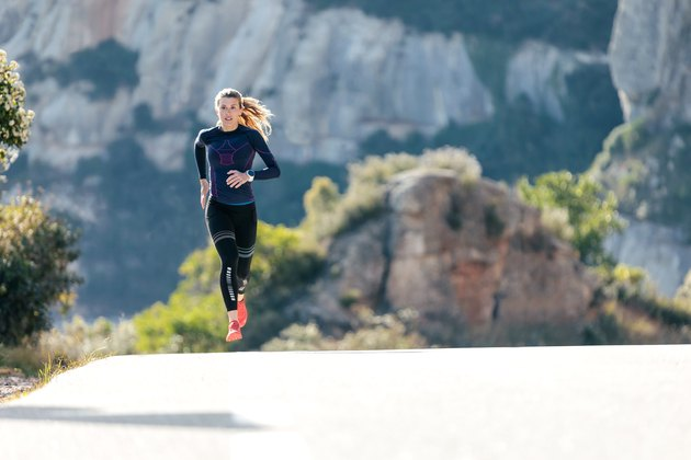 Sporty young woman running on mountain road in beautiful nature.