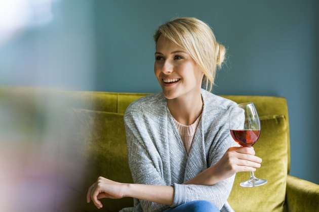 A smiling woman holding a glass of red wine and sitting on a green sofa
