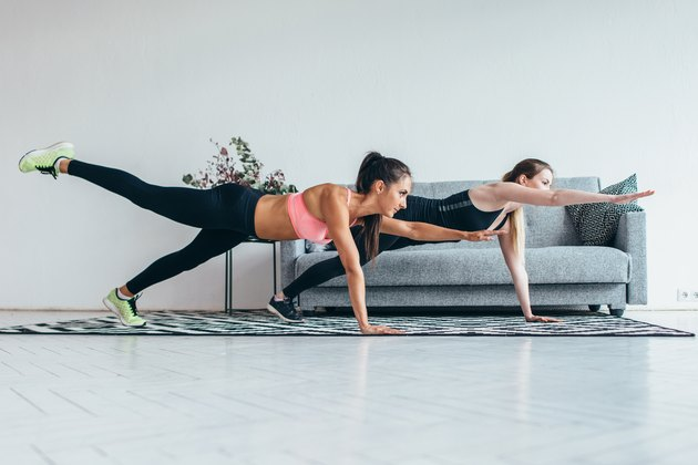 Fit women doing one hand one leg plank exercise workout at home.