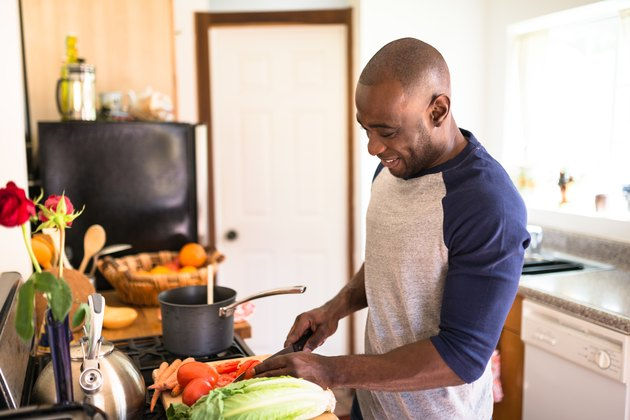 A man cooking in his kitchen to lose weight at home