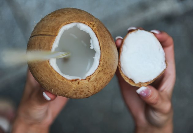 Close-Up Of Hands Holding Coconut Drink