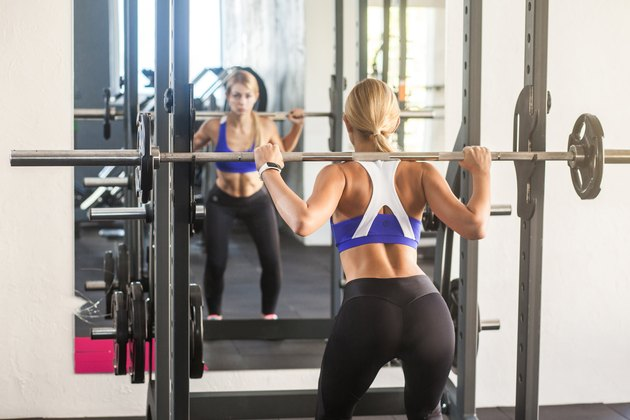 Woman holding bar, doing squats, looking mirror