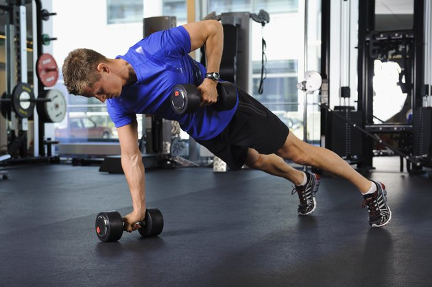 Man exercising in gym, doing renegade rows, to build muscle