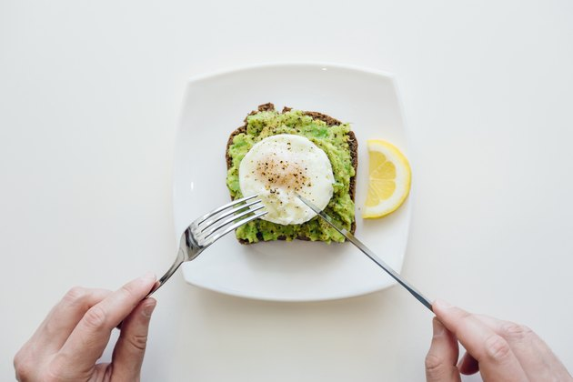 Eating breakfast with avocado toast and egg from personal perspective point of view