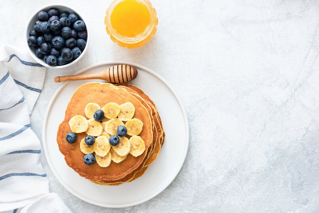 Buttermilk Pancakes with banana, blueberries and honey on concrete background