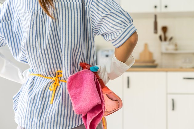 Back view of a woman with cleaning supplies standing in her kitchen with her hands on her hips